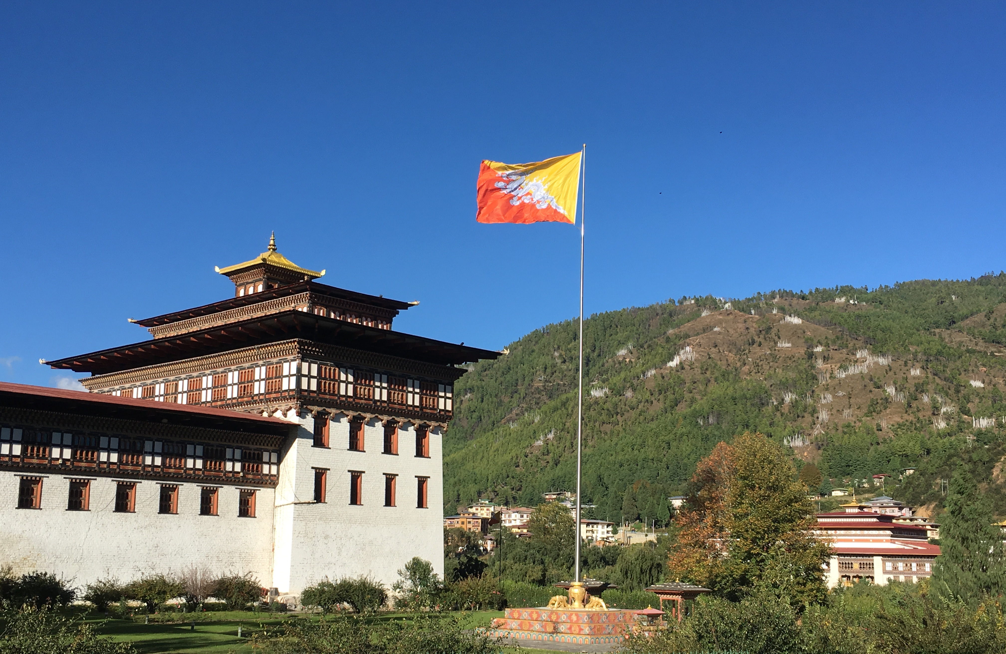 Bhutan flag in front of building.  Photo: Adhy Aman | International IDEA